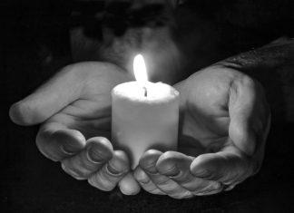 Brennende Kerze in den Händen
